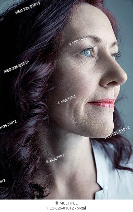 Close up portrait serious Caucasian mature woman with curly burgundy red hair looking away