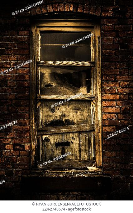Vintage grunge details on a wooden decrepit window framed on a haunted brick house. Spooky old homes