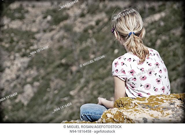 Blonde girl teen, back looking at the landscape in Gátova, Valencia, Spain