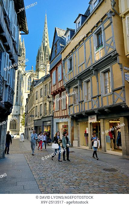 Cathedral of Saint Corentin seen beyond shops on Rue Kereon in the mediaeval city centre of Quimper, Finistere, Brittany, France