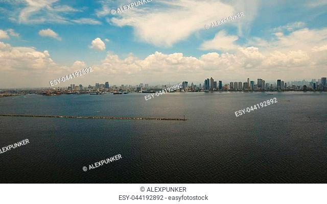 Aerial view of Manila city. Fly over city with skyscrapers and buildings. Aerial skyline of Manila. Modern city by sea, highway, cars, skyscrapers