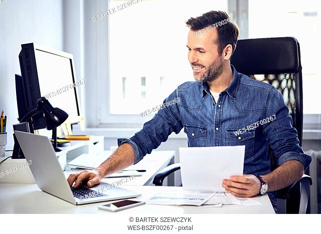 Smiling man holding document and using laptop at desk in office