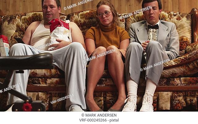 MS Overweight  man wearing pajamas, holding bag of chips sitting by nerdy couple on sofa, Orem, Utah, USA