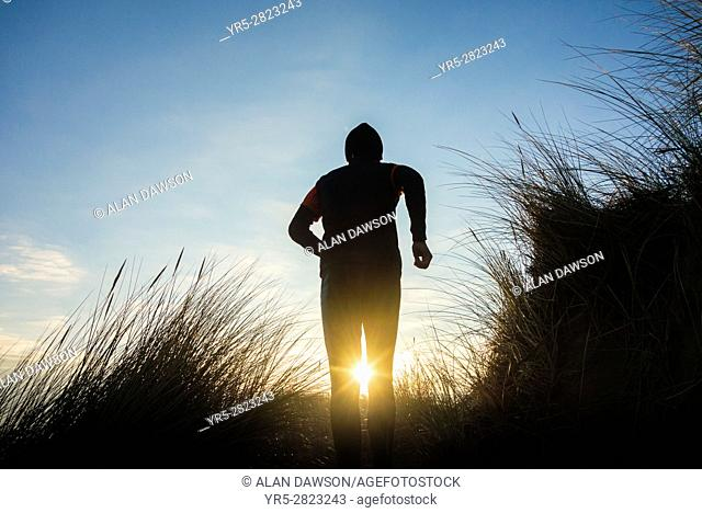 Seaton Carew, north east England. United Kingdom. Man running on trail through sand dunes on Seaton Carew beach at sunrise