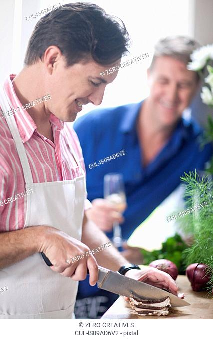 Mature man chopping red onion, man in background