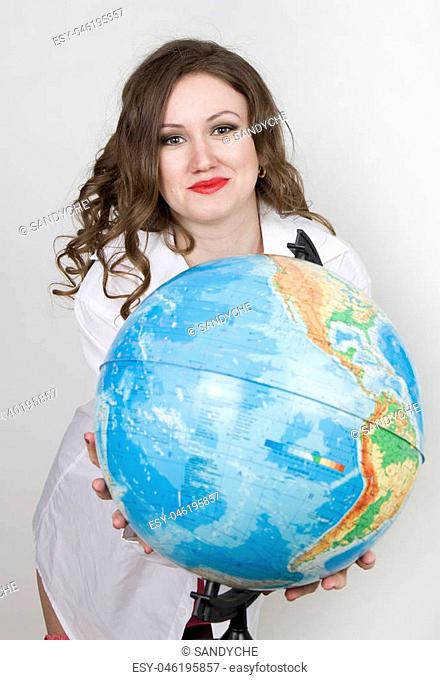 Young beautiful woman in white mens shirt with globe