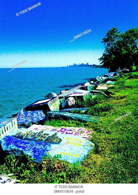 Graffiti covered seawall blocks, Evanston, Illinois. Downtown Chicago on horizon
