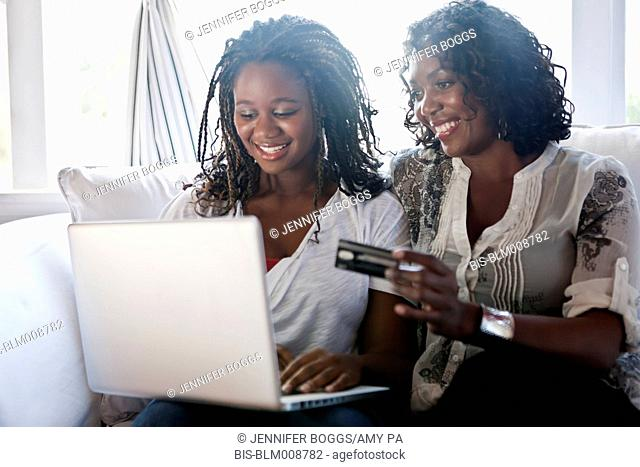 Black mother and daughter shopping online with credit card