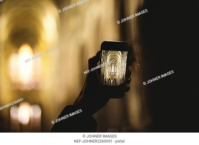 Close-up of hand taking picture of church interior