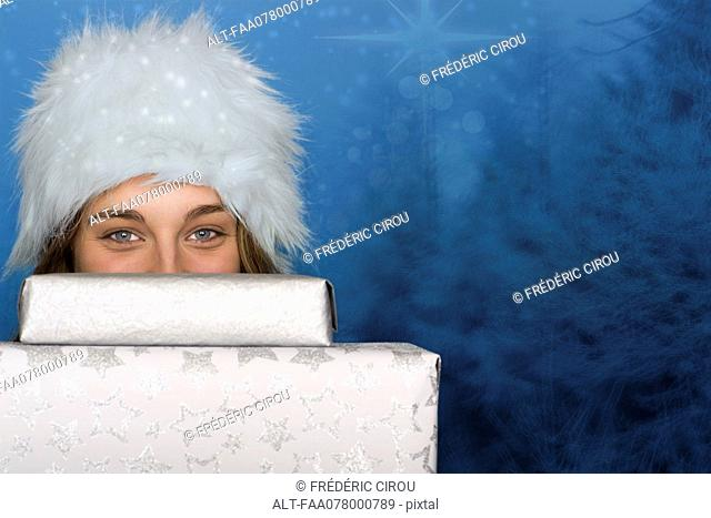 Young woman peeking over stack of Christmas gifts, portrait