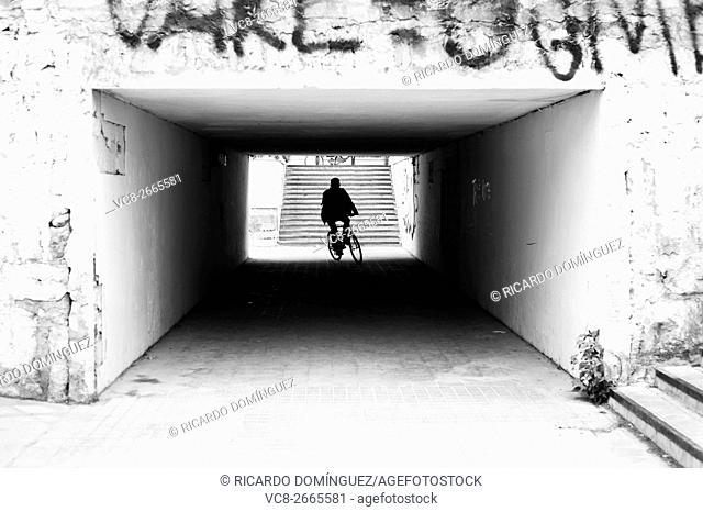 Silhouette of people crossing a sidewalk tunnel. Valencia, Spain