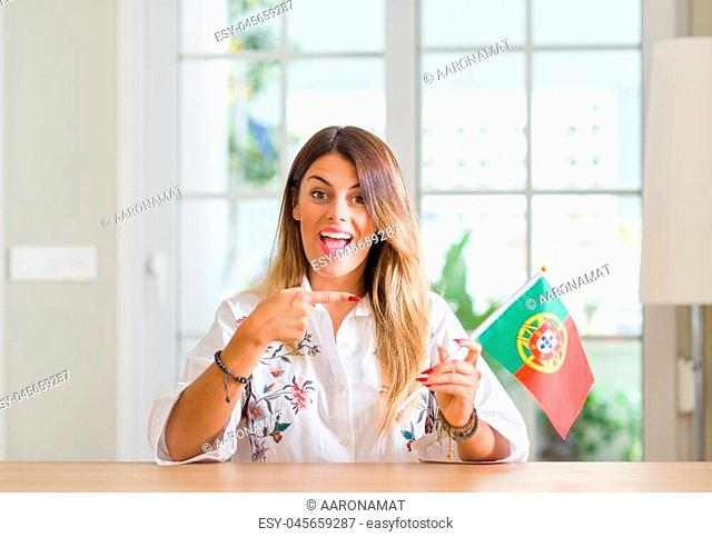 Young woman at home holding flag of Portugal very happy pointing with hand and finger