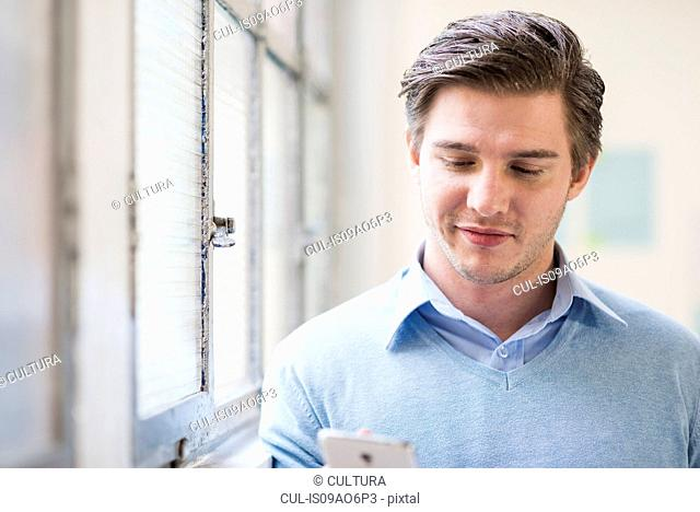 Young businessman texting on smartphone in office