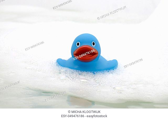 Blue duck in a bathtub, surrounded by soap