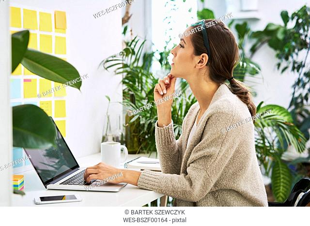Young woman with laptop on desk looking at adhesive notes on the wall
