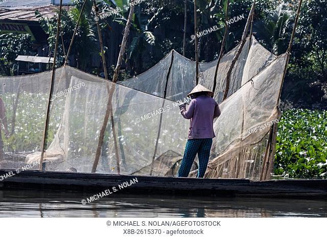 Woman checking fish nets on Binh Thanh Island at Sadec, Mekong River Delta, Vietnam