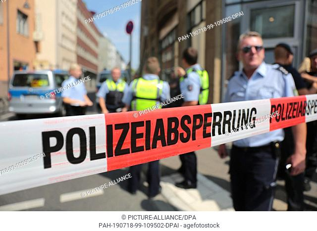 18 July 2019, North Rhine-Westphalia, Cologne: Policemen are standing in front of a residential building in the city centre behind a barrier tape