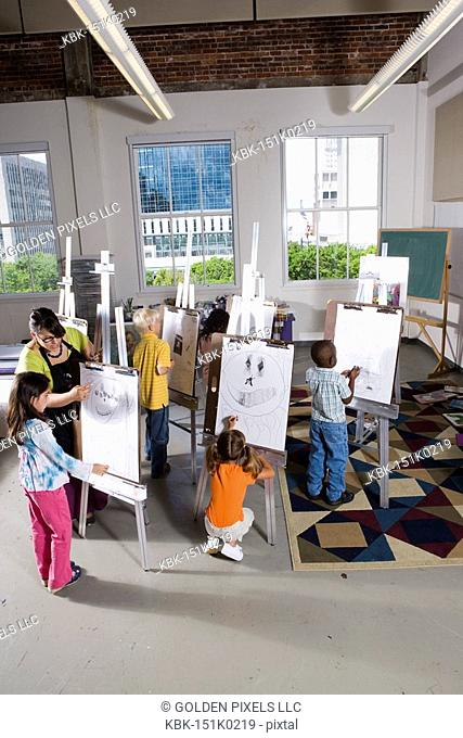 An art teacher with her student drawing on easels in art class