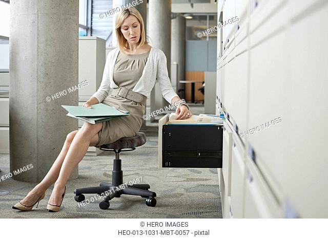 Businesswoman searching files in filing cabinet at office