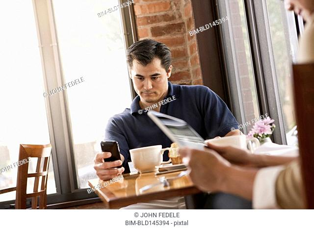 Chinese man using cell phone in cafe