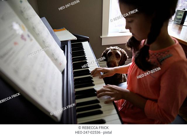 Dog watching girl play piano