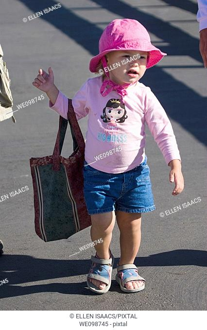 Two year old girl in a pink outfit walking along while holding a bag that is too big for her  She seems to be playing grownup in carrying her mother's bag