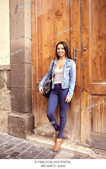 Pretty young girl looking at the camera while leaning against old wooden doors smiling and her hair loose in jeans and denim jacket