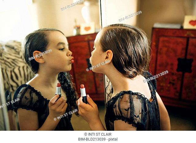 Mixed race girl applying lipstick in mirror