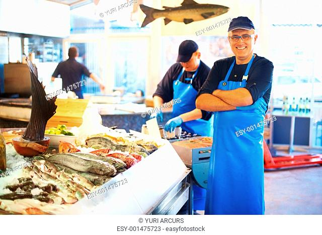 Smiling fishmonger standing with arms folded