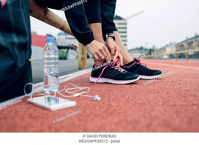 Woman on tartan track tying her shoes