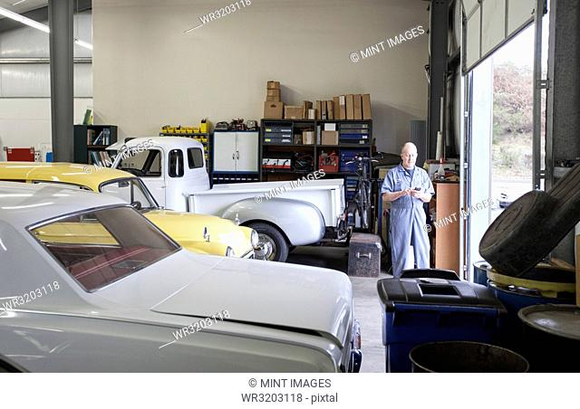 A mechanic standing in an auto repair shop, with a line of classic cars