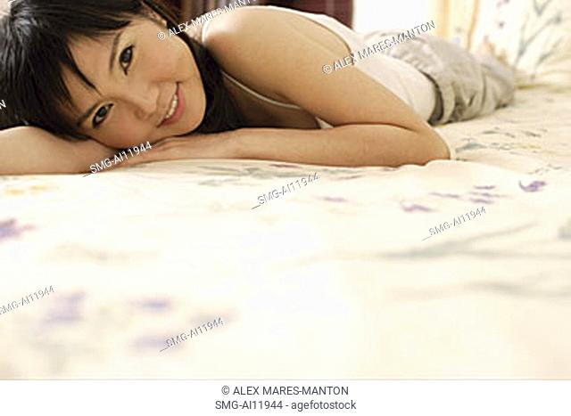 Young woman lying on bed, looking at camera