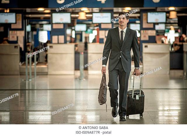 Young man with wheeled suitcase in airport