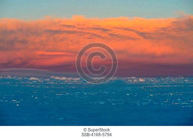 ANTARCTICA, WEDDELL SEA, FAST ICE WITH SNOW HILL ISLAND IN BACKGROUND, PINK CLOUD AT SUNSET