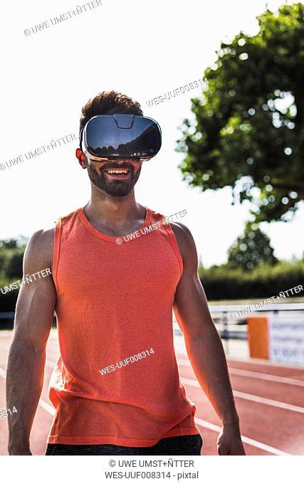 Smiling athlete on tartan track wearing virtual reality glasses