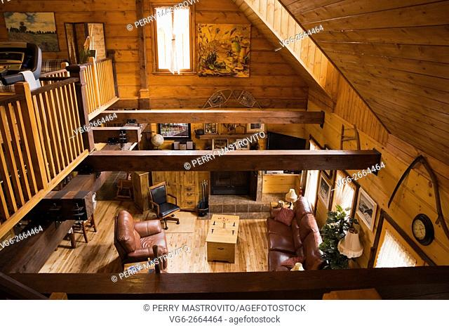 View of the living room from the mezzanine inside a Canadiana cottage style residential stacked white pine log home, Laurentians, Quebec, Canada