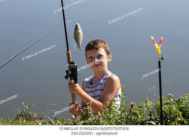 Teen catches fish in the pond at the bait