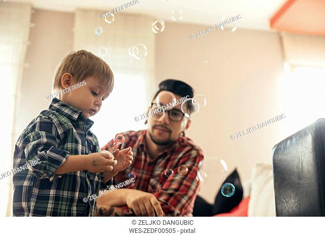 Father and son blowing soap bubbles at home