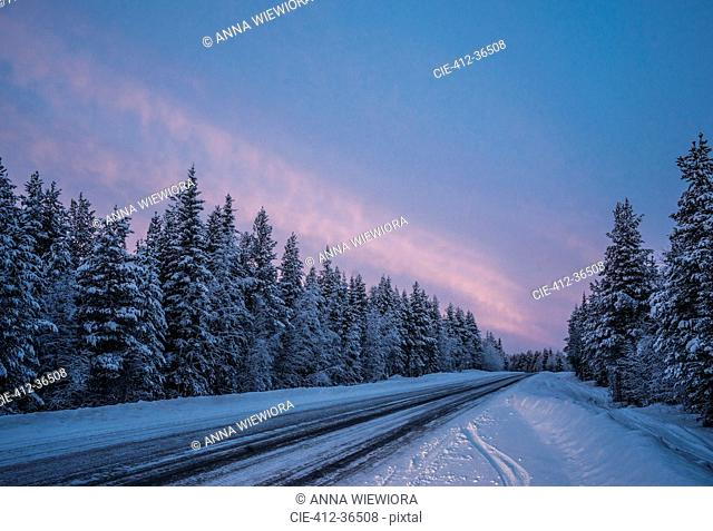 Remote winter road through snow covered forest trees, Lapland, Finland