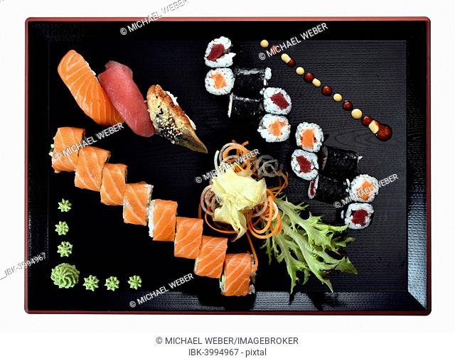 Sushi dish with Maki, Uramaki, Nigiri with salmon, tuna, eel, fresh ginger, wasabi, on a Japanese wooden plate