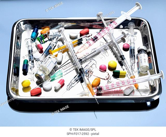 A variety of medical syringes, ampules and drugs on a medical tray