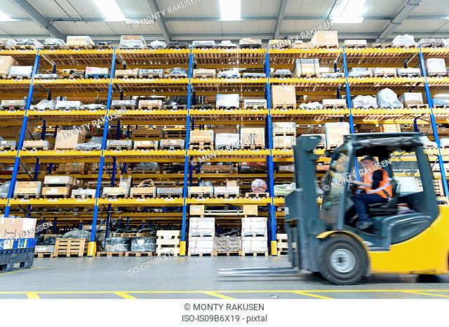 Female forklift truck driver in train works warehouse