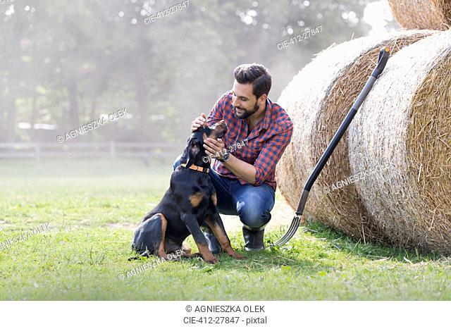 Man petting dog next to rolled hay bales