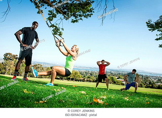 Young woman and trainer with lunge rope in field