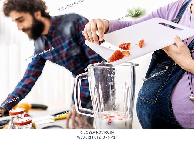 Pregnant woman preparing smoothie with fresh strawberries, partial view