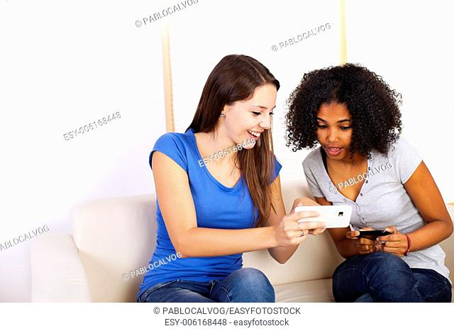 Portrait of two cute girls using mobile phones on a sofa