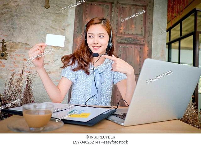 Portrait of woman customer service worker, call center smiling operator with phone headset. Young female business model.,showing blank name card