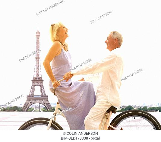 Caucasian couple riding bicycle near Eiffel Tower, Paris, Ile