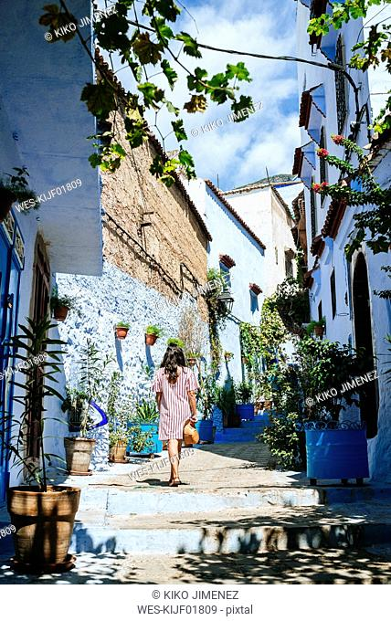 Morocco, Chefchaouen, back view of woman walking alley upstairs