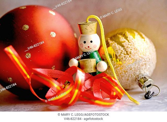Red and gold Christmas balls with little wood accordian player and ribbon on white damask satin